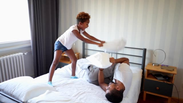 Père frapper l'enfant dans une bataille d'oreillers drôle