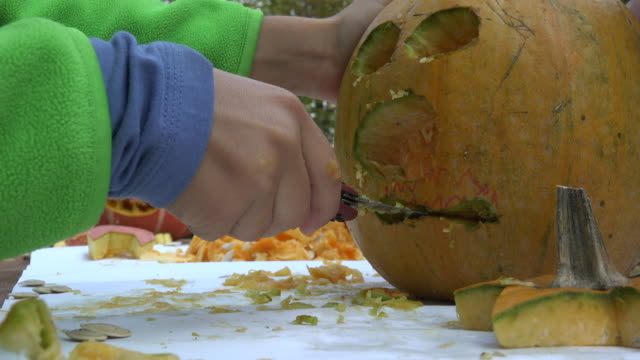 child holding a small pocket knife and carving a halloween pumpkin - carving knife stock videos and b-roll footage