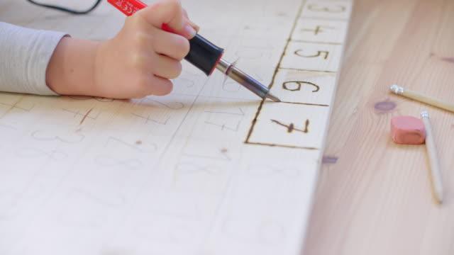vídeos y material grabado en eventos de stock de ld niño sosteniendo una herramienta de quema de madera y escribiendo en una tabla de madera - number 8