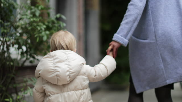 vidéos et rushes de child holding mother's hand walking down street - famille avec un enfant