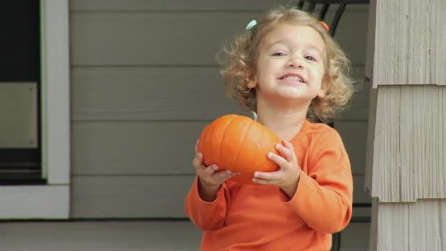 stockvideo's en b-roll-footage met child holding pumpkin - tanden op elkaar klemmen