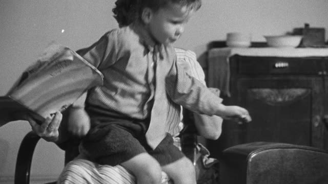 vidéos et rushes de 1950 montage child hopping off foster mother's lap and playing on the floor with spinning top toy as social worker and foster mother observe / united kingdom - orphelinat