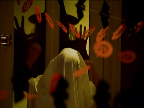 a child in a ghost costume runs away from the silhouette of a witch at the front door of a halloween party - halloween stock videos & royalty-free footage