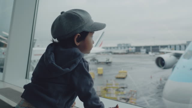 child in airport near window looking on airplanes and waiting for time of flight - commercial airplane stock videos & royalty-free footage