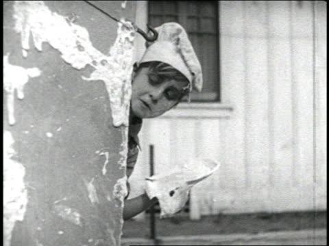 stockvideo's en b-roll-footage met b/w 1920 child in chef's hat looking around corner / pies get thrown into his face / short - gluren