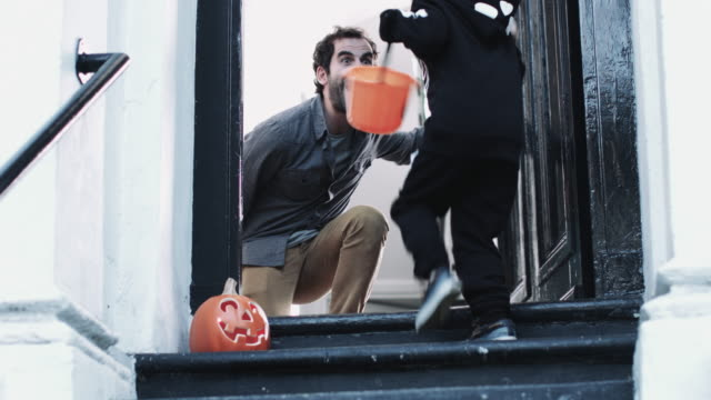 child in halloween costume receiving candy at door - halloween stock videos & royalty-free footage