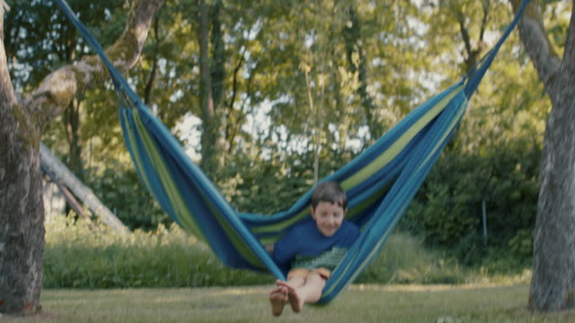 child in hammock in backyard - schwingen stock-videos und b-roll-filmmaterial