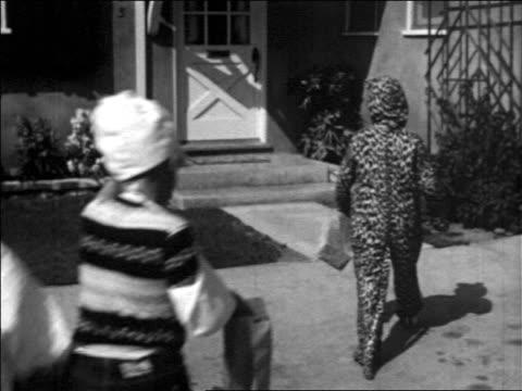 vídeos de stock, filmes e b-roll de b/w 1957 child in leopard costume gestures to group of children + they walk to door of house - 1957