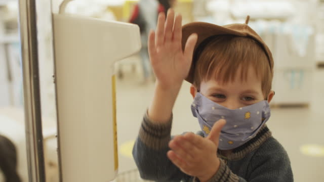 child in protective mask using hands sanitizer in a shopping mall or a store - soap dispenser stock videos & royalty-free footage