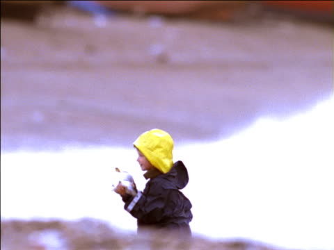 child in rain hat carries fish up beach to fisherman dressed in yellow dungarees, uk - waterproof clothing stock videos and b-roll footage