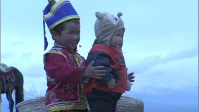 child in traditional mongol clothing looks after younger sibling, bayanbulak grasslands. - baby boys stock videos and b-roll footage