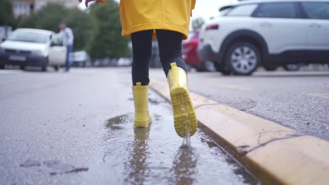 child in yellow rubber boots splashing water in puddles outdoors on a city street - footwear stock videos & royalty-free footage