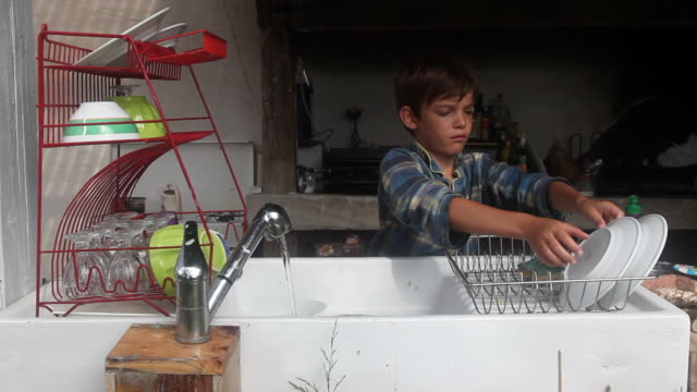 child is doing the dishes - diska bildbanksvideor och videomaterial från bakom kulisserna