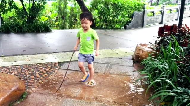 stockvideo's en b-roll-footage met kind is voeten spelen van slow-motion in het water - alleen jongens