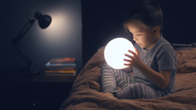 a child is sitting on the bed and holding a glowing moon in his hands. - curiosity stock videos & royalty-free footage