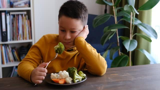 vidéos et rushes de l'enfant est très malheureux d'avoir à manger des légumes. il y a beaucoup de légumes dans son assiette. il déteste les légumes. - contestant