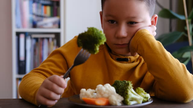 child is very unhappy with having to eat vegetables. there is a lot of vegetables on his plate. he hates vegetables. - disgust stock videos & royalty-free footage