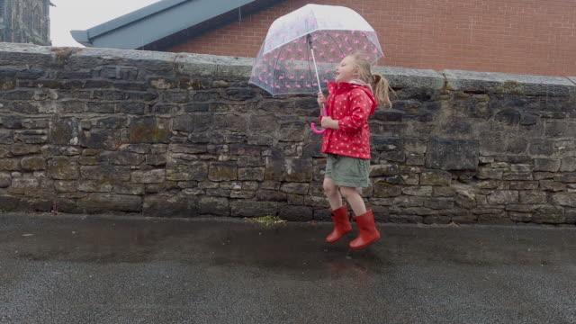 vidéos et rushes de child jumping in puddles - seulement des petites filles