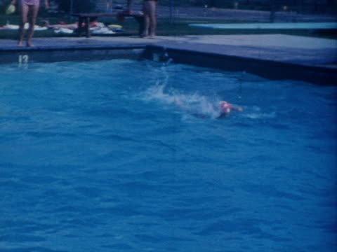 A child jumps into a swimming pool and begins swimming.