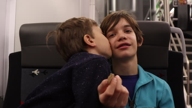 child kisses his brother on a train