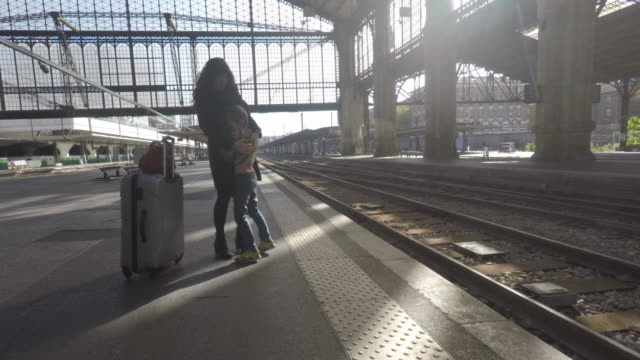 child kissing his mother on the platform of a train station