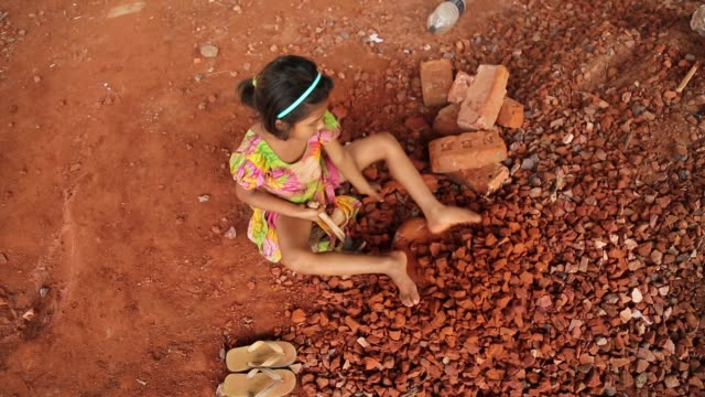 A child labor break bricks in Dhaka Bangladesh on March 06 2018 Child labor work for helping her family with her mother With over half of the...
