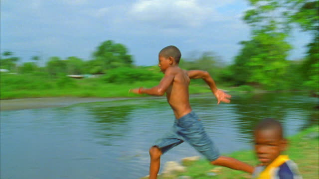 a child lands near a friend as he does a back flip from a dock into a river. available in hd. - バク転点の映像素材/bロール