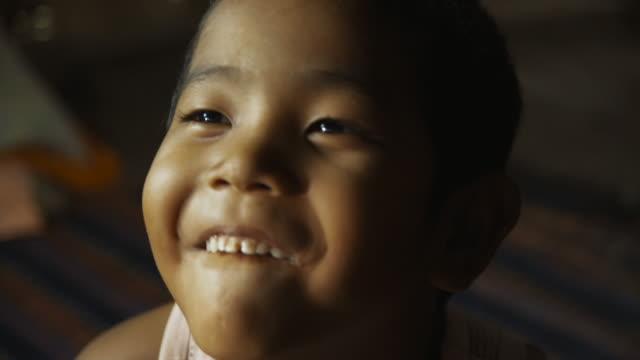 c/u child (boy) laughing and doing funny faces - ミャンマー点の映像素材/bロール