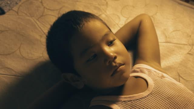 m/s child (boy) laying down, falling asleep - occhi chiusi video stock e b–roll