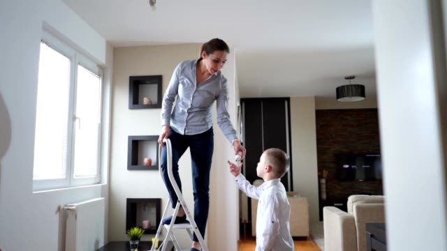 child learning how to change a light bulb from his mother - changing lightbulb stock videos & royalty-free footage