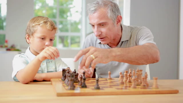 child learning to play chess with his grandpa - 余暇 ゲームナイト点の映像素材/bロール