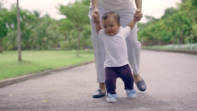 vidéos et rushes de l'enfant apprend à marcher avec la mère - béton