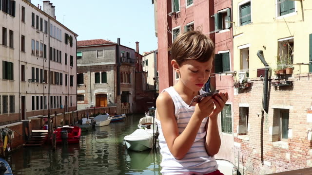 child looking at a cartel in front of a canal in venice - discovery stock videos & royalty-free footage