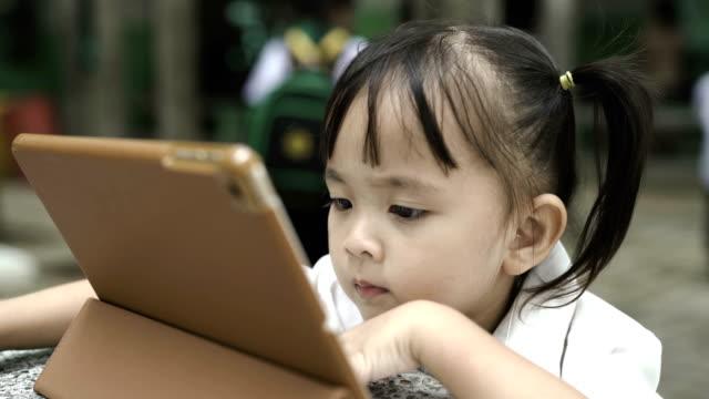vidéos et rushes de enfant regardant sur tablette numérique - synthpop
