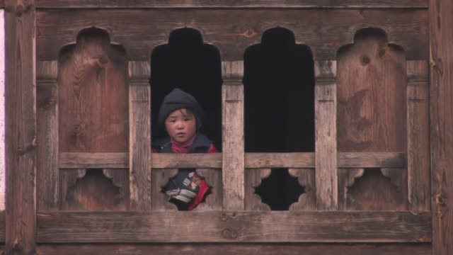 a child looking out the wooden window of a traditional house. - bhutan stock videos & royalty-free footage