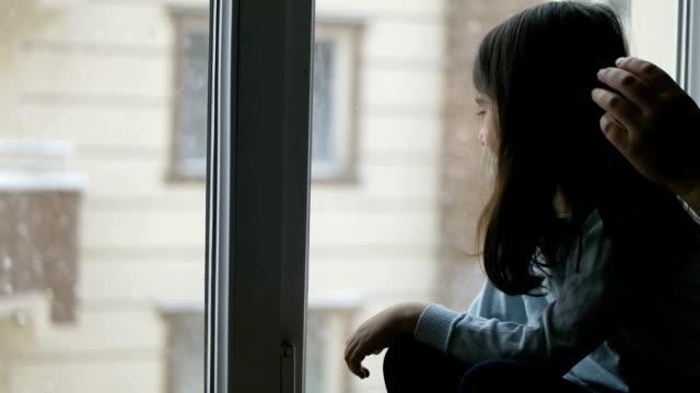 vídeos y material grabado en eventos de stock de niño mirando por la ventana durante la tormenta de nieve en invierno día - detrás