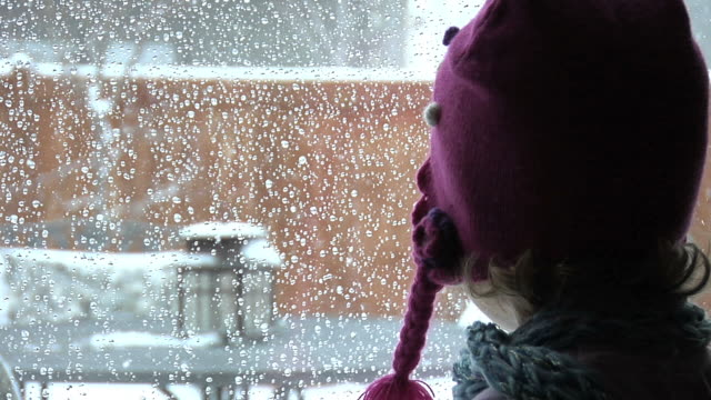 stockvideo's en b-roll-footage met child looking out window - muts