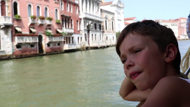 child looks at the buildings of the Grand Canal of Venice on a ferry