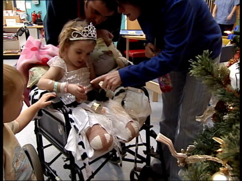 child loses legs following misdiagnosis tony cross holding baby sister milly bv cross family looking at christmas tree in hospital mss lydia affixing... - family tree stock videos and b-roll footage