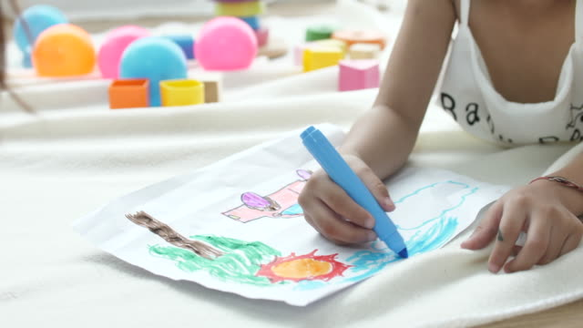 Child lying down drawing white sheets