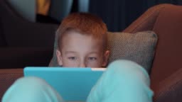 Child lying in arm chair and watching cartoons on pad