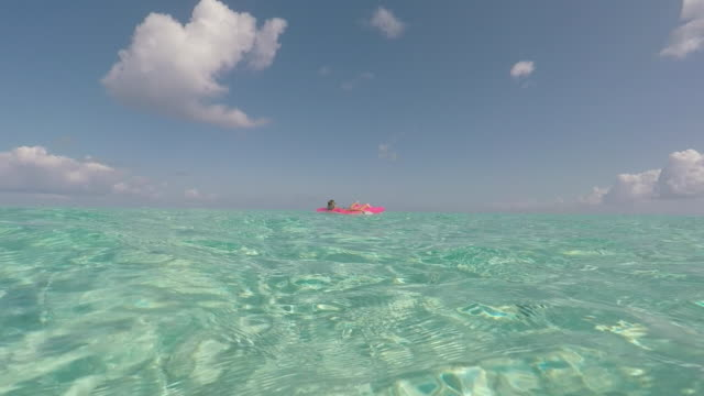 child lying on an air mattress on the sea - inflatable stock videos and b-roll footage