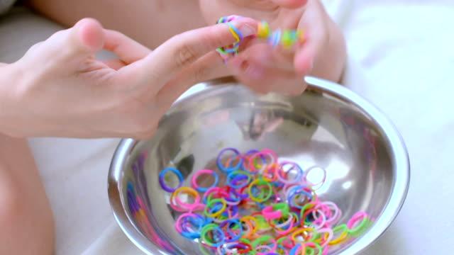 vídeos de stock e filmes b-roll de child making  bracelets - fazer