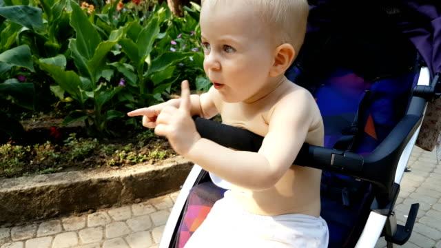 vídeos y material grabado en eventos de stock de niño haciendo muecas, sentado en la silla de paseo - hacer muecas