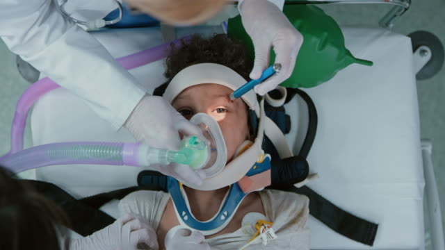 Child on a spinal board receiving anesthetics through a face mask