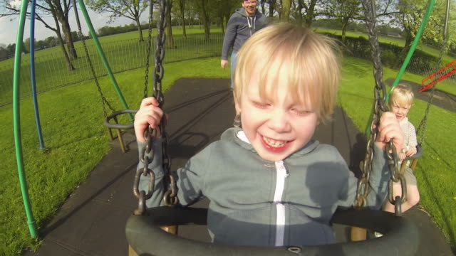 child on a swing in the park - kinderspielplatz stock-videos und b-roll-filmmaterial
