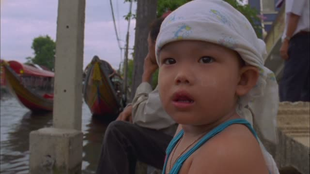 vidéos et rushes de child on banks of chao phraya river stares into camera available in hd. - coiffe traditionnelle