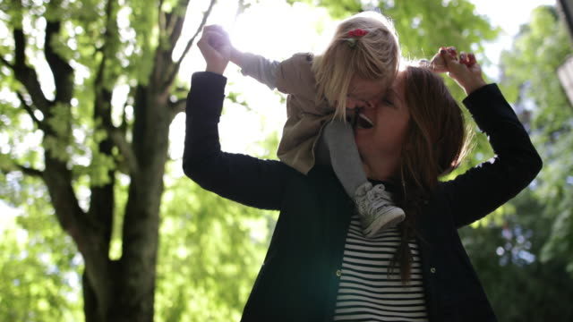 child on mother shoulders in park - toddler stock videos & royalty-free footage