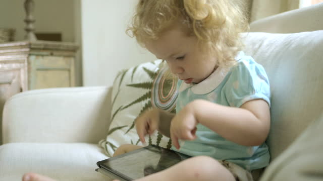 child on sofa playing with digital tablet. - mid length hair stock videos & royalty-free footage