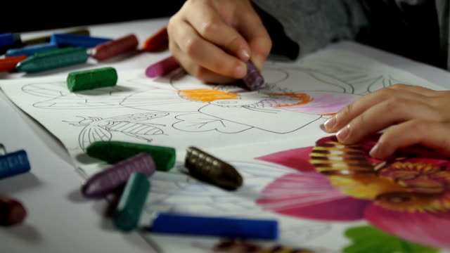 child paints coloring with crayons - schulkind nur jungen stock-videos und b-roll-filmmaterial